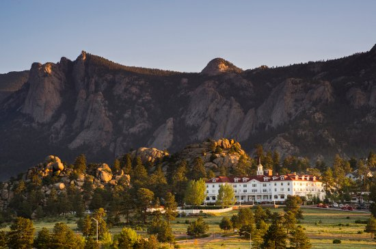 A picture of the Stanley hotel at the base of steep Colorado mountains.